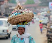 A woman carries a basket on her head as she walks along a street in Oniyanrin community in Ibadan, South-west, Nigeria, November 7, 2012