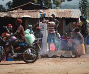A motorcyclist rides past villagers fetching water at a public borehole in Jiwa village, outskirt of Nigeria's capital Abuja November 10, 2012.