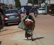 A woman hawks sugar cane through a street in Romi district in Nigeria's northern city of Kaduna November  12, 2012.
