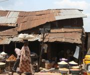 A woman hawks past a roadside market near a makeshift bus-stop in Ibadan, South-west, Nigeria November 7, 2012.