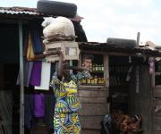 A woman hawks past a roadside makeshift kiosk at kudeti district in Ibadan, South-west, Nigeria November 7, 2012.