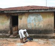 A woman spreads clothes in front of a building with a painting inscription advertising a native doctor at kudeti district in Ibadan, South-west, Nigeria November 7, 2012.