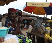 Women selling foodstuffs wait for customers as they sit near a umbrella promoting family planning at a roadside market in Mapo district in Ibadan, South-west, Nigeria November 7, 2012.