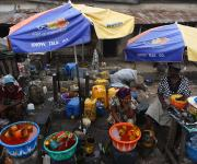 Women selling palm oil in bowls wait for customers under umbrellas promoting family planning in Beere district, in Ibadan, South-west, Nigeria November 7, 2012.