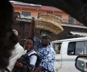 A woman and her daughter are pictured through the window frame of a car as they ride on a motorcycle along a road in Ibadan, South-west Nigeria, November 7, 2012