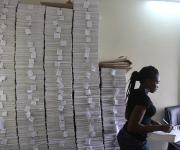 A family panning data input officer, Theresa Johnson works near a stark of questionnaire piled up inside a room at the measurement, learning and evaluation office at the central business district in Nigeria's capital Abuja November 10, 2012.