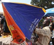 A trader, Emmanuel Ezeh tries to set up a NURHI designed umbrella used for promoting family planning, in a market in Kakuri district in Nigeria's northern city of Kaduna, November 12, 2012.