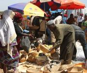 A man selling calabash attends to a customer in a market in Kakuri district in Nigeria's northern city of Kaduna, November 12, 2012.