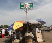 A NURHI umbrella promoting family planning is seen near a signboard showing designated routes Kawo motor park in Nigeria's northern city of Kaduna, November  13, 2012.