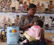 A nursing mother and family planning mobilizer, Docas Olabanji tends her baby as she waits for the opening of ante natal session at Orolodo primary health centre in Omuaran township in Nigeria's central state of Kwara, November 5, 2012.