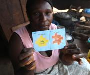 A fish monger, Grace Olayiwola, displays her go card after she was referred by a family planning mobilizer, during a visibility parade near Orolodo primary health centre in Omuaran township in Nigeria's central state of Kwara, November 5, 2012.