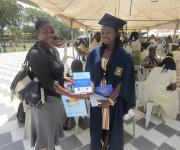 Social Mobilizer presents a congratulations gift, complete with information about family planning, at the Uni-Ilorin Tanke graduation